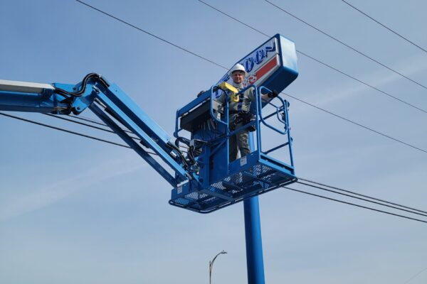 OHM repairs an outdoor sign